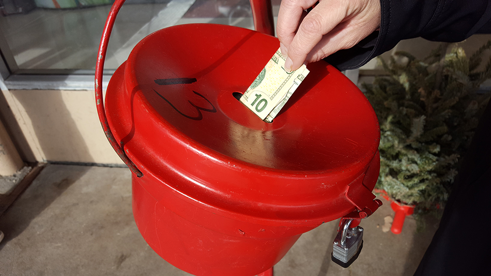 red donation kettle and 10 -dollar bill