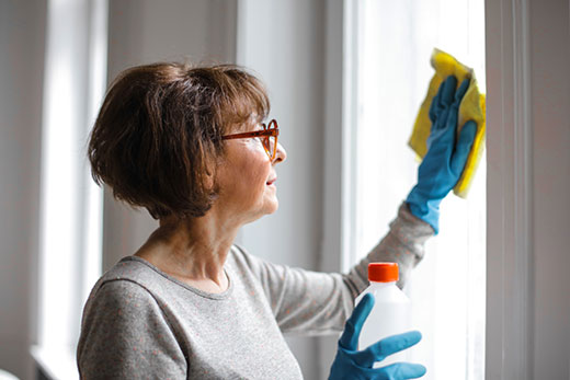 woman wearing gloves and cleaning window