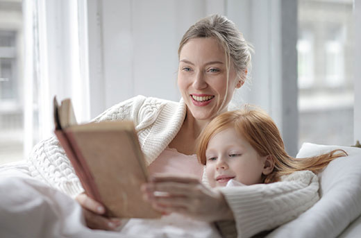 mother and daughter reading on a couch